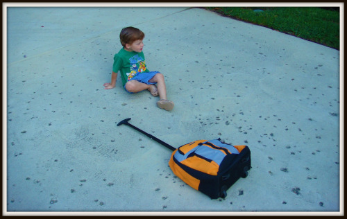 Preschooler sits with backpack