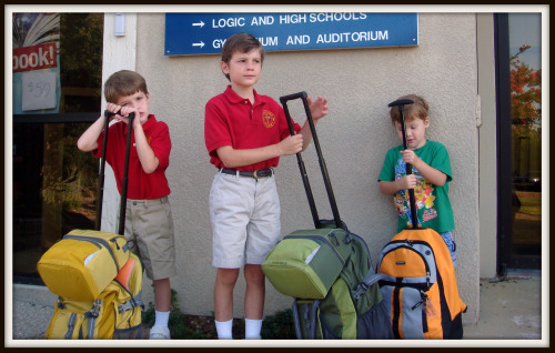 3 boys stand in front of school on first day