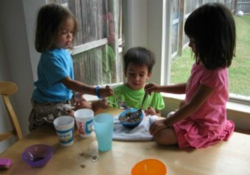 three kids mixing foods at table