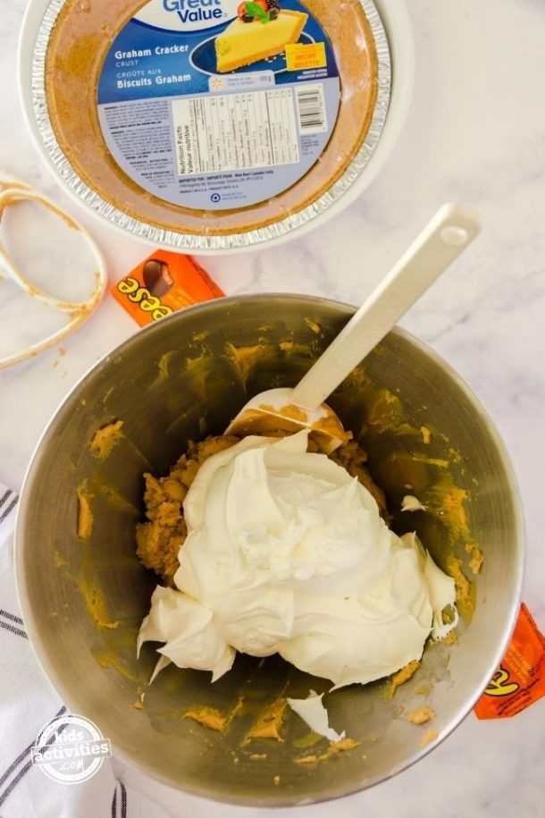Mixing bowl with peanut butter filling and cool whip on top with a spatula to stir with.