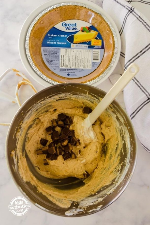 Peanut butter pie filling in a mixing bowl with chunks of Reese Peanut Butter Cups on the top.