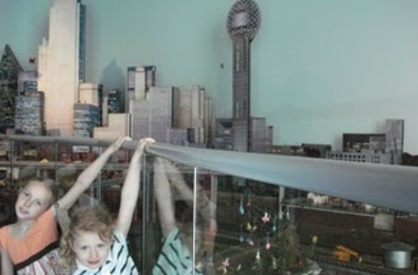2 kids looking at model of dallas skyline