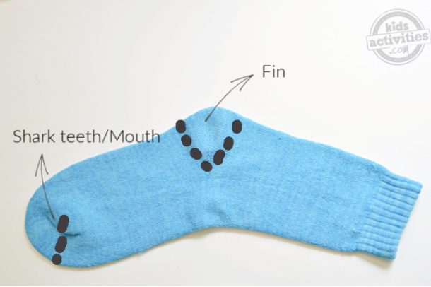 A blue sock used to make shark puppet and the areas are marked for cutting