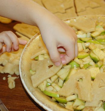 A child is placing letter A cut out of pie crust on top of apples