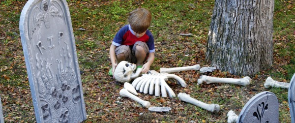 Boy arranges bones of a skeleton for halloween decorations