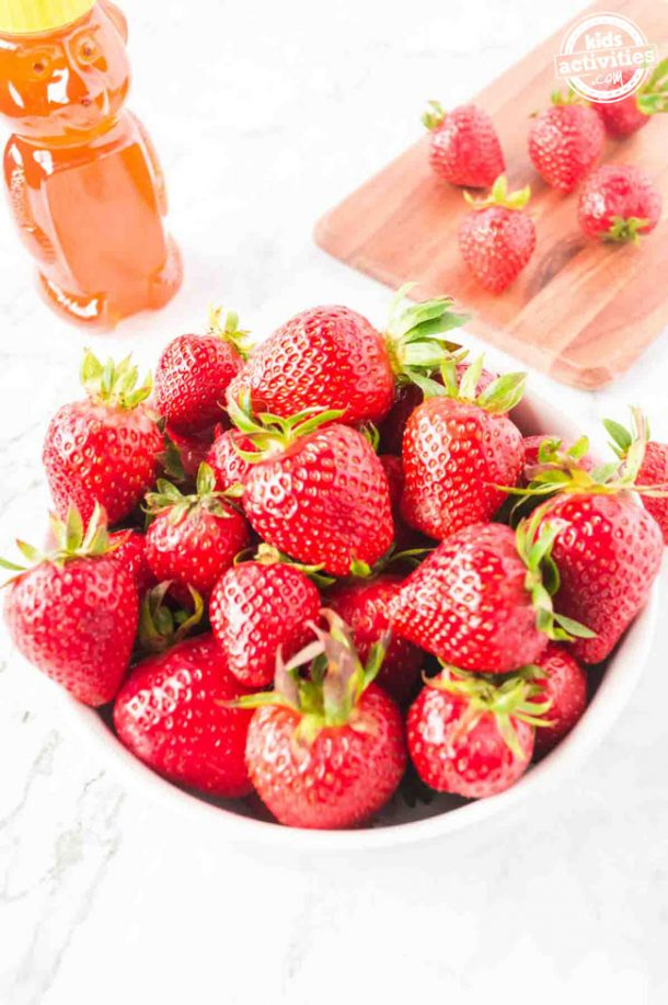 A bowl of whole red strawberries and a bottle of honey.