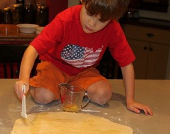boy paints butter on cinnamon roll dough