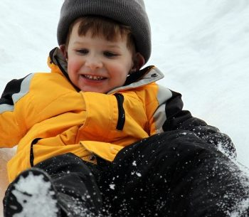 boy slides down hill in favorite color coat