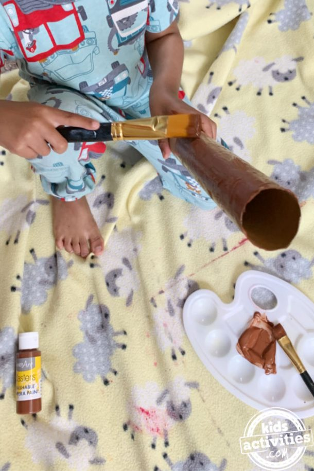 Toddler painting an empty paper roll for preschool craft to make snake