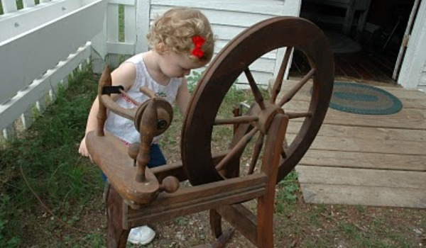 preschool girl playing with old spinning wheel