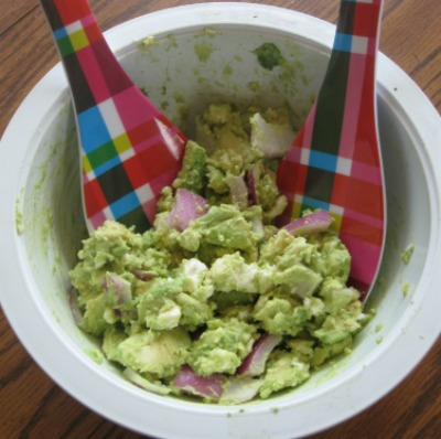avocado salad with red plaid spoon in white bowl
