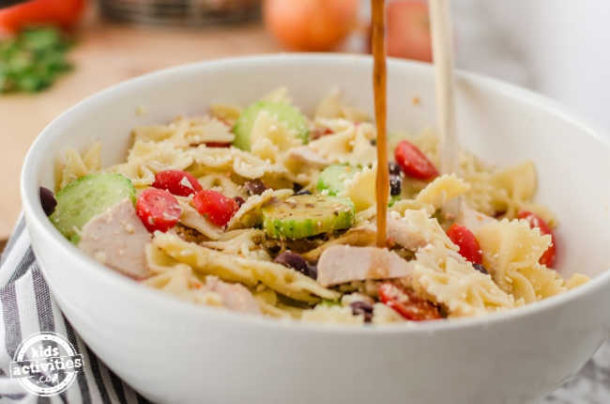 Salad Dressing being drizzled over a bowl of Easy Greek Salad with Chicken.