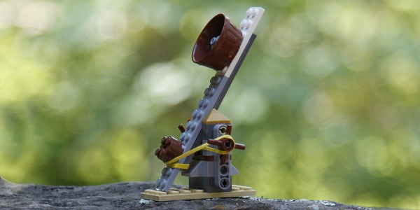 Catapult made out of LEGO bricks finished and sitting on green background