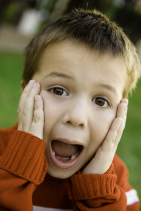 boy in orange sweater screaming with hands on face