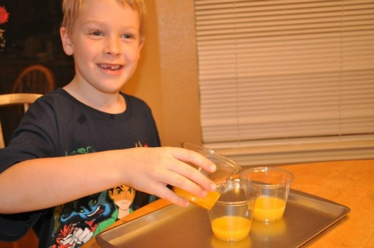 boy pouring orange juice