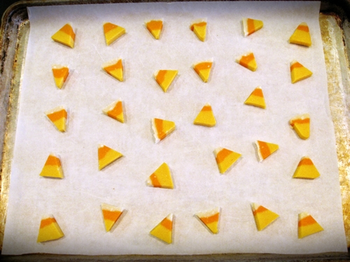 The orange, yellow, and white candy corn looking sugar cookies on parchment paper.