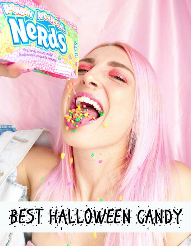 A young woman with pink hair is pouring a box of Nerds candy into her mouth.