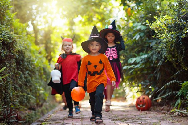 A group of three children dressed in halloween costumes and holding plastic pumpkin buckets are walking down the sidewalk during daylight hours.