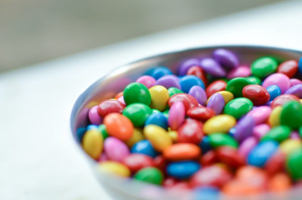 A bowl of colorful chocolate M&Ms that have purple, green, blue, yellow, red, orange.