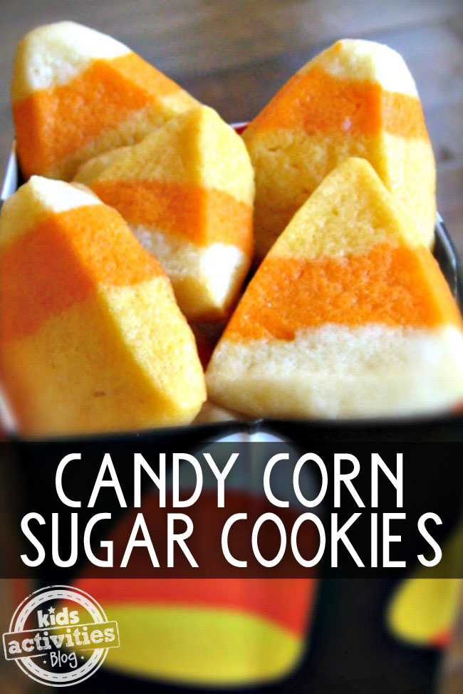 Candy corn sugar cookies in a candy corn black bowl, that are yellow, orange, and white.