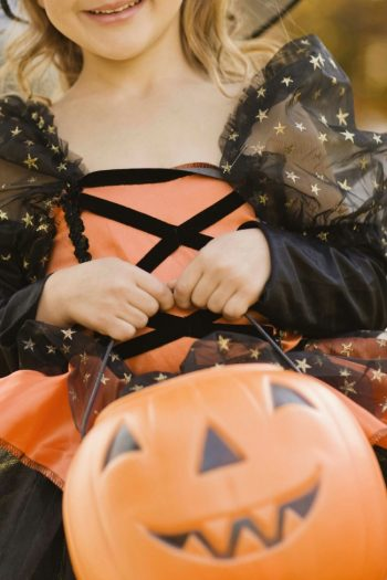 A girl dressed up as a witch is holding an orange plastic pumpkin bucket ready to trick-or-treat in her neighborhood.