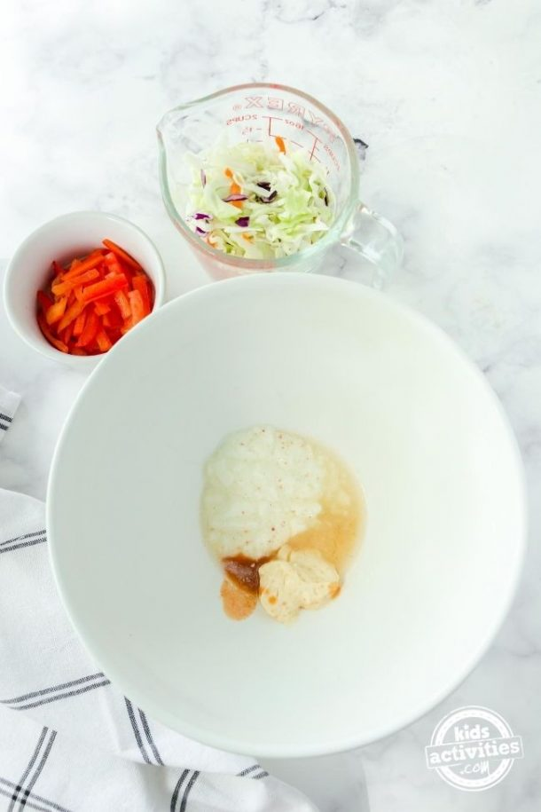 White bowl filled with coleslaw dressing ingredients inside with a bowl of coleslaw and red peppers beside.