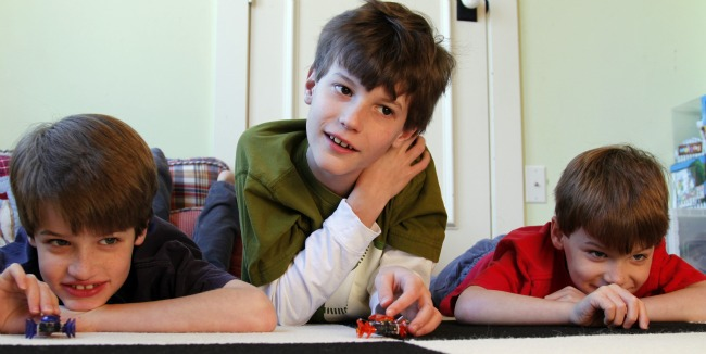 three boys playing with hex bugs