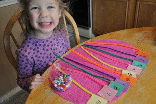 little girl with pipe cleaner numbers