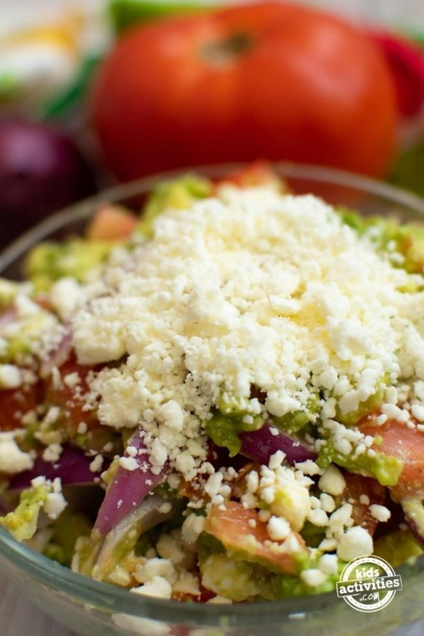 Summer Avocado Salad in a bowl with feta cheese sprinkled on the top.