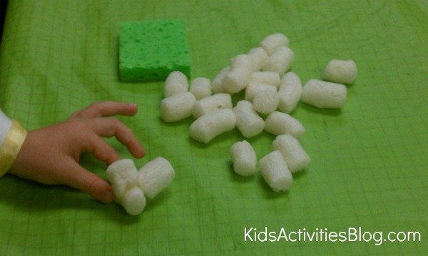 child playing with packing peanuts