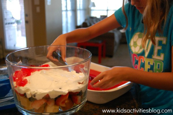 child making 4th of July dessert trifle by layering in large glass bowl