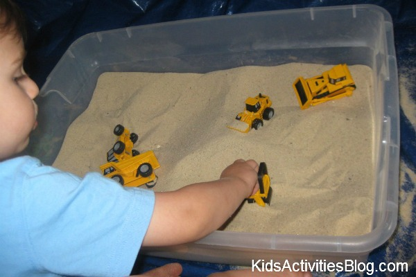 little boy construction vehicles sand