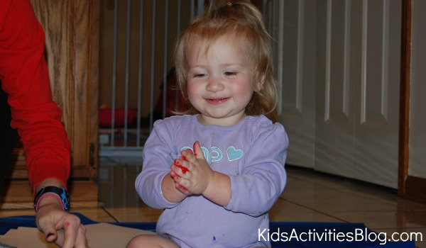 little girl with red painted hands