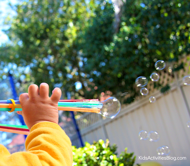 small child using a bubble shooter wand to blow bubbles across the backyard fence
