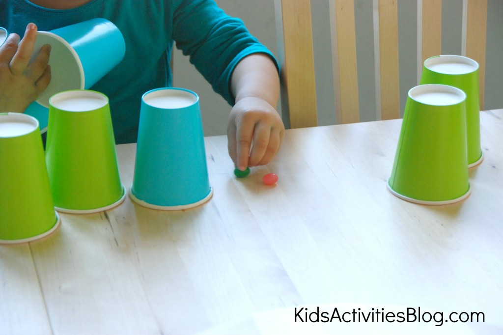 halloween candy cup guessing game with a child finding green and pink gummies under blue and green paper cups.