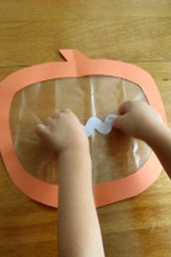 make a halloween pumpkin window cling using lots of colorful ribbon
