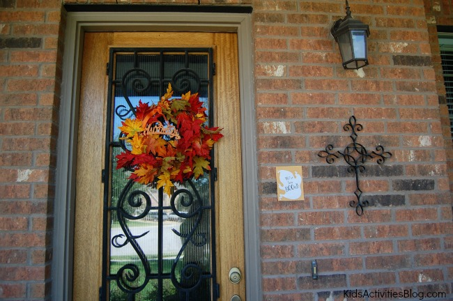 Halloween surprise! The booed card is sitting right next to this beautiful iron and glass door with an autumn leaf wreath with reds, golds, and oranges.