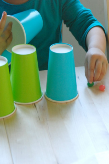 Child found gummies underneath blue and green paper cups