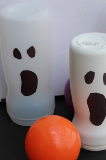 Home made ghost bowling pins are about to be hit by an orange ball that kinda looks like a pumpkin