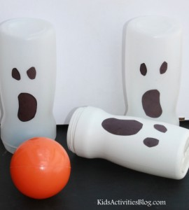 Halloween themed bowling game features white creamer containers with ghost faces made out of black construction paper. An orange ball is meant to look like a pumpkin.