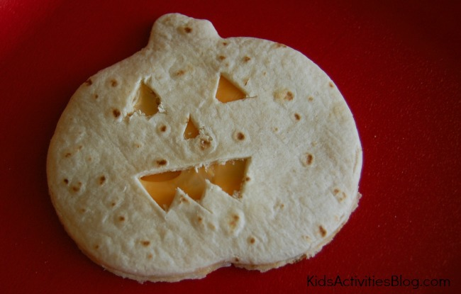 A tortilla is cut in the shape of a jack o lantern pumpkin, with cheese showing through the face.