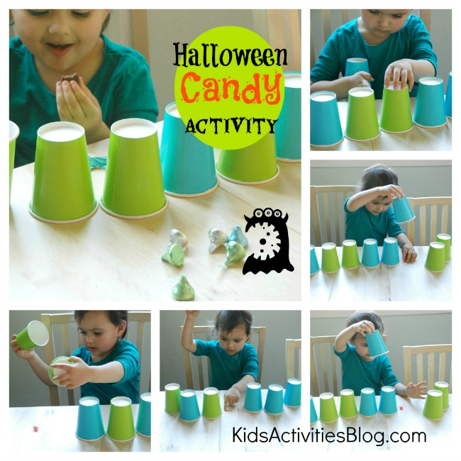 Halloween Candy Activity- a little girl is finding leftover Halloween candy under blue and green paper cups.