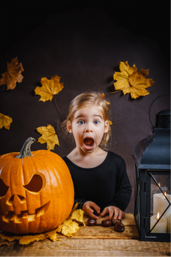 little girl next to a jackolantern is surprised by all the halloween activities for kids