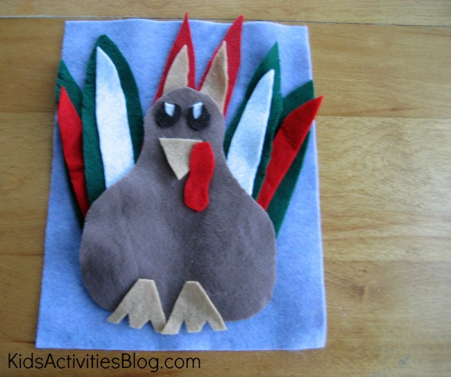 Thanksgiving Preschool activity making a brown, red, white, and green turkey with felt on a blue felt background.