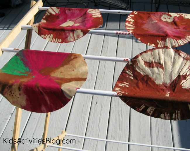 Thanksgiving turkey crafts drying over a rack in the sun. The wet muffin liners covered in green, red, and brown paint is drying.