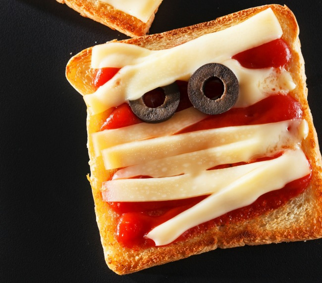 tomato sauce is covered by strips of mozzarella, and two olives serve as eyes for this mummy sandwich