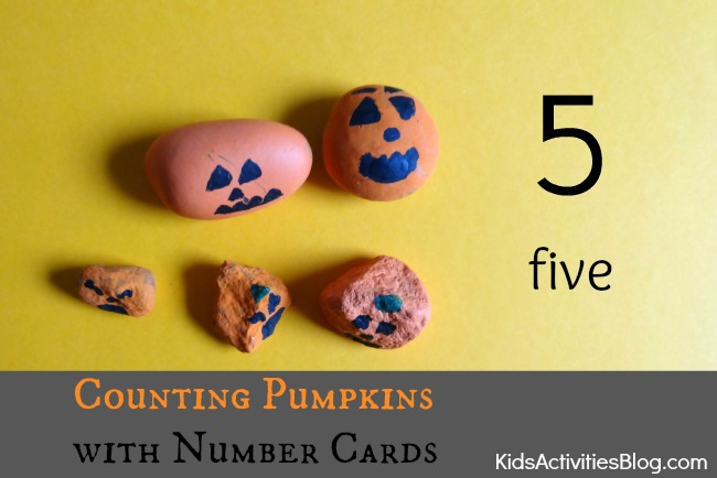 Cute painted pumpkin rocks used for the counting pumpkin games with the number card that has sqaures