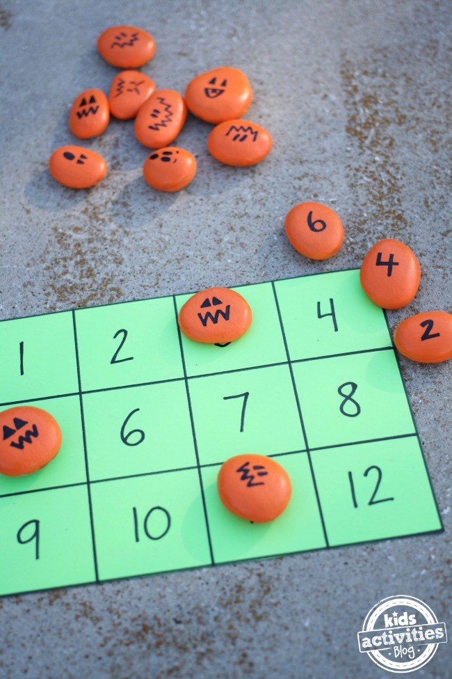 Pumpkin math activity with a number card and painted jack o lantern rocks.