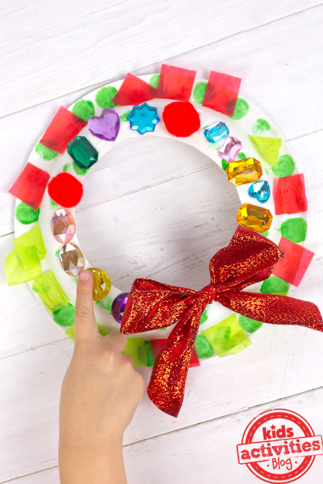 Christmas wreath for kids with purple, yellow, blue, and green gems, red tissue paper and a red bow.