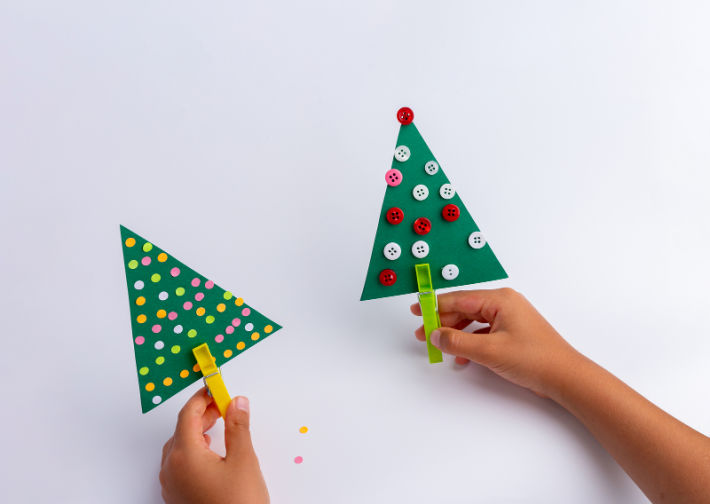 paper christmas tree craft - decorated craft paper triangles with clothes pin trunks